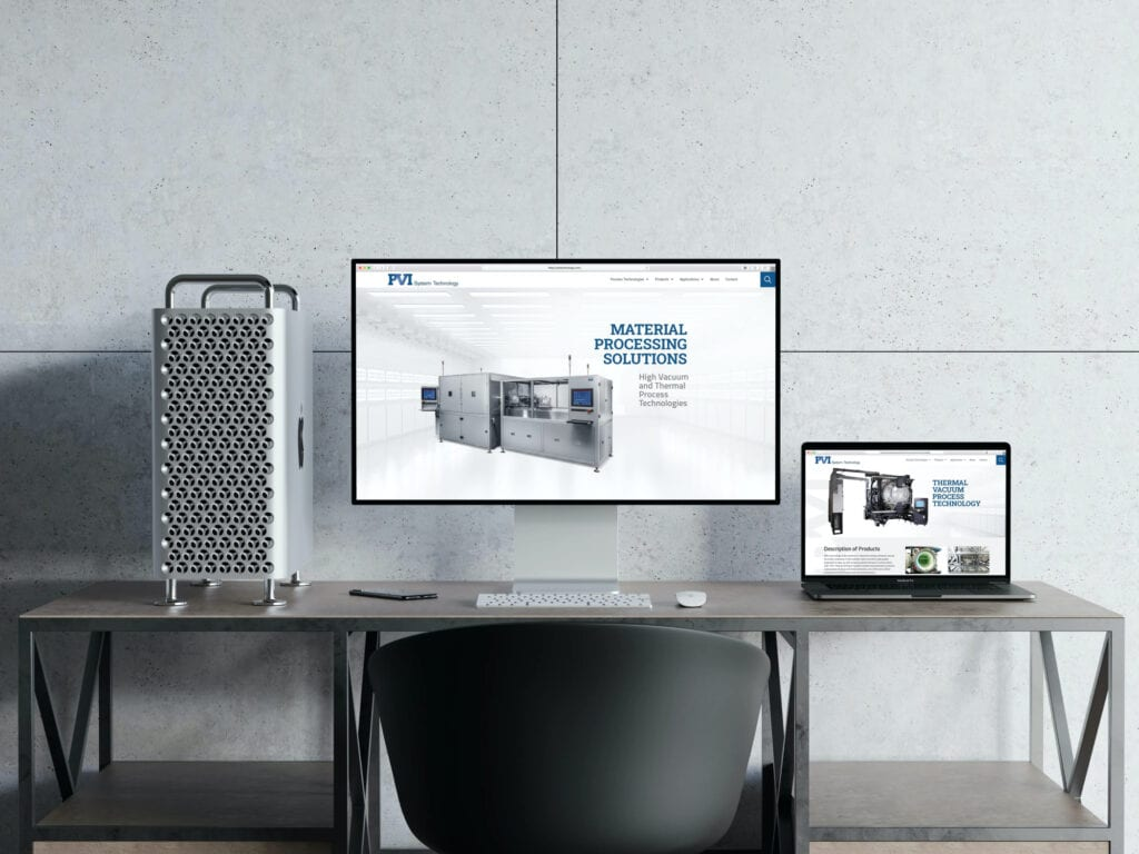 A Mac pro and laptop sit on a clean desk in a concrete room, pvitechnology.com is on the screen