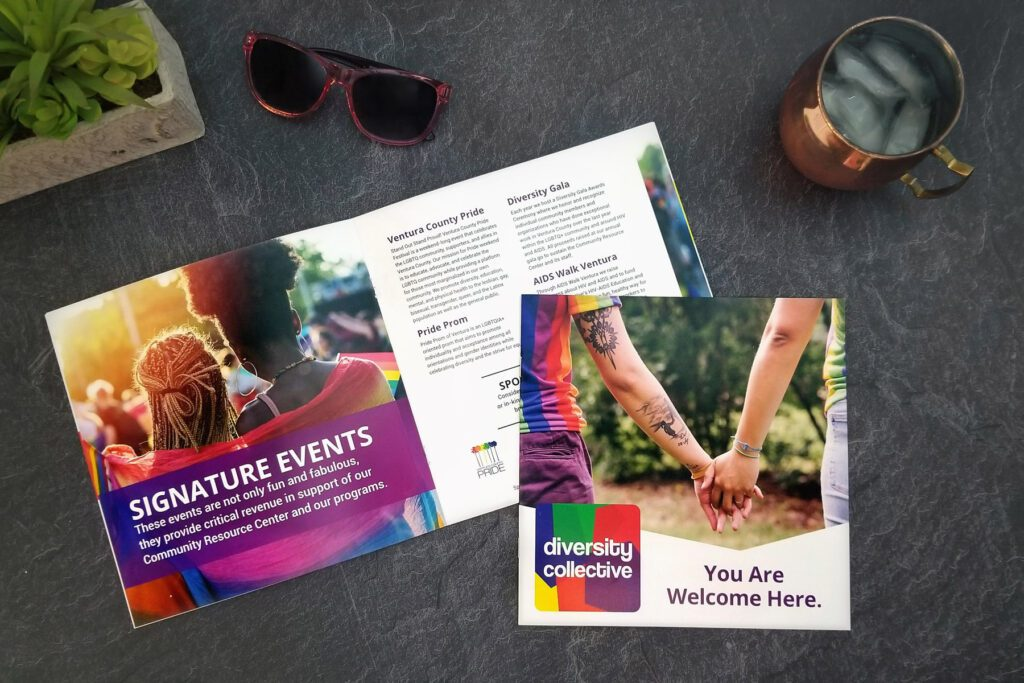 Two copies of the Diversity Collective brochure are displayed on a slate counter, next to a pair of sunglasses and a moscow mule