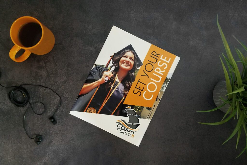 VC College brochure, on a dark slate table next to a cup of coffee and a potted plant